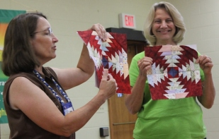 Kathy Wickam and Cathy Russell displaying the Pineapple blocks for the 2017 Quilt Show Raffle Quilt.