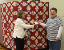 Kathy Wickham presents the winning ticket to Connie Hogan, who purchased it at the Spring 2017 Guild Quilt Show