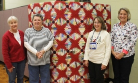 Left to Right: Cathy Fandel, who professionally quilted the quilt, Connie Hogan, raffle quilt winner, Kathy Wickham, raffle quilt organizer, and Cathy Russel, Guild President